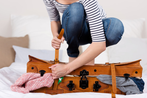 Midsection of young woman packing suitcase on bed