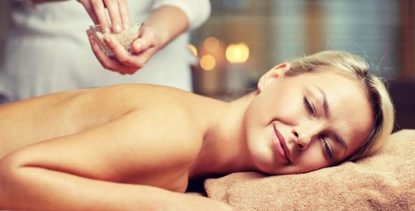 people, beauty, spa, massage and relaxation concept - close up of beautiful young woman lying with closed eyes and therapist holding salt bowl in spa